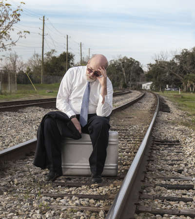 tired businessman: Jobless senior businessman sits on suitcase on railroad train tracks pondering his uncertain future.