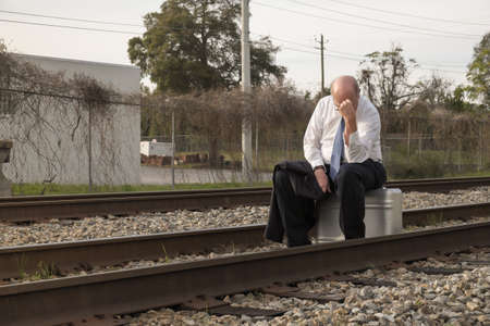 leaving: Senior businessman with no job and no prospects rests on his old suitcase along a railroad train track, holding his head, afraid and worried.