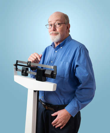 heavy weight: Senior caucasian man weighing himself on vertical weight scale  He looks pleased and optimistic   Stock Photo