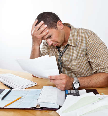 pay desk: Worried exhausted young man sits at desk paying bills, head in hands. Stock Photo