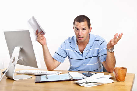 Young man at desk with computer and stacks of bills to be paid, with open checkbook. White background.  photo
