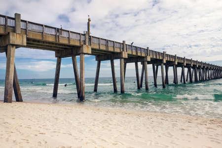 Pensacola Beach Pier, Pensacola, Florida in de winter. Surfers in wetsuits gezien in de verte.