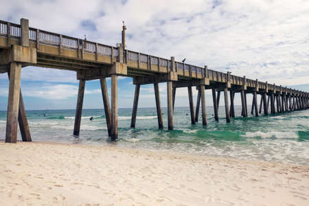 Pensacola Beach Pier, Pensacola, Florida in winter. Surfers in wetsuits seen in the distance.