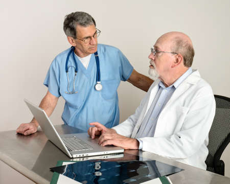 Two mature medical doctors at laptop computer discussing patient's scans.
