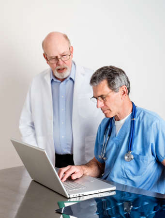Two mature medical doctors at laptop computer discussing patient's scans photo