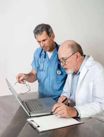 Two male doctors talking seriously, with laptop computer. photo