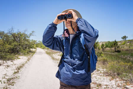 parka: Mature man in hat, backpack and windbreaker standing on a path in an arid landscape looking through binoculars