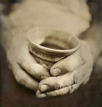 man s: Vintage Style Photo of Man s Worn Hands Holding Pottery Cup
