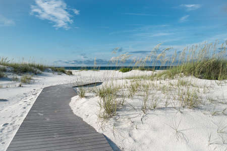 Rustic beach boardwalk through white sand dunes at a pristine Florida beach  Stock Photo
