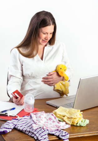Cute pregnant woman at her laptop computer surrounded by baby clothes, shopping online for more baby supplies photo
