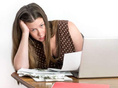 worries: Pretty worried young woman sitting at laptop with stack of bank statements and unpaid bills, looking at camera.