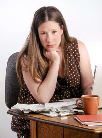 unmarried: Pregnant mother-to-be reads bills and bank statements while seated at a desk with stacks of unpaid bills next to laptop computer. She looks calm and confident.  Stock Photo