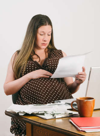 paying the bills: Pregnant mother-to-be reads bills and bank statements while seated at a desk with stacks of unpaid bills next to laptop computer. She looks surprised and slightly worried.