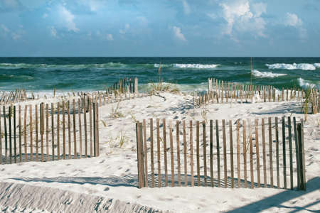 Beautiful landscape or seascape of white sand beaches, puffy clouds, cheerful sand fences and emerald tropical waves with frothy breakers on a sunny day at Pensacola, Florida beach