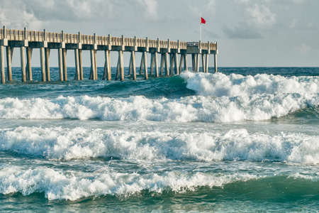 Waves crash around fishing pier at Pensacola Beach, Florida