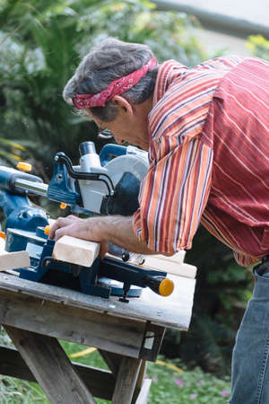 miter: Closeup of mature man sawing lumber with sliding compound miter saw outdoors.