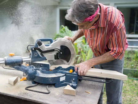 Closeup of mature man sawing lumber with sliding compound miter saw outdoors, sawdust flying around Standard-Bild