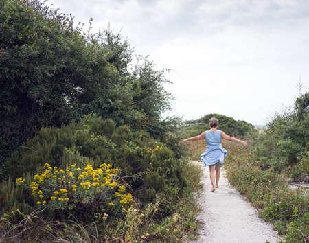 national holiday: Happy mature senior woman walking sandy path through beach sand dunes