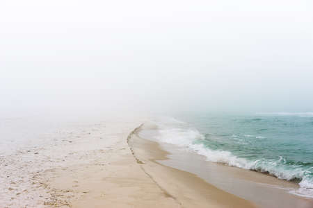 restful: Soft pastel landscape photo of waves breaking on a pristine, peaceful, unpopulated beach.