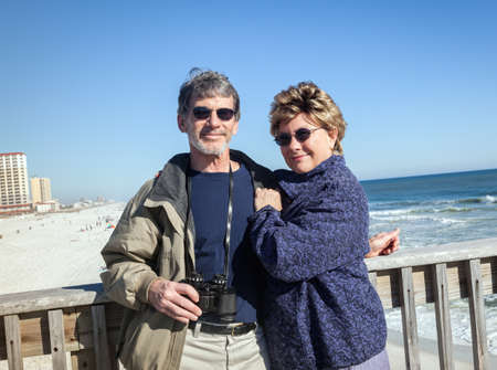 Happy mature couple on Forida fishing pier hugging photo