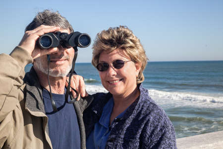 destination wedding: Happy senior couple enjoying themselves at a beautiful beach on their winter or spring vacation with binoculars and sunglasses