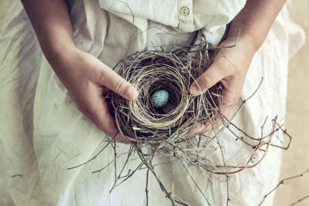 Vintage toned closeup of girl holding wild bird nest and blue egg
