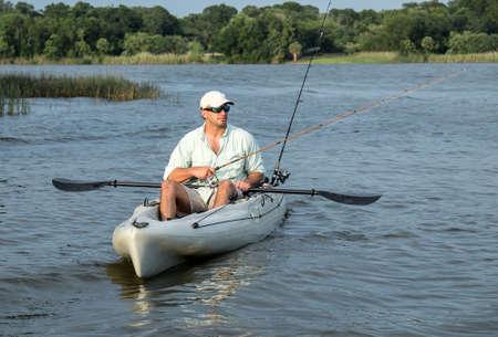 男は、夕暮れ時に美しい日のカヤックからの釣りを楽しんでいます