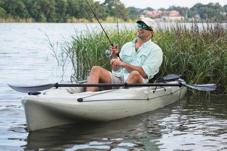 Man vissen vanaf kajak op een mooie dag bij zonsondergang