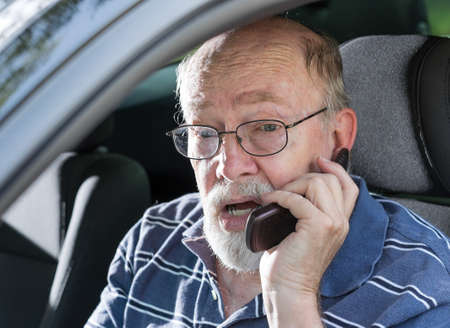 Angry elderly man yelling on cell phone in car  Stock Photo