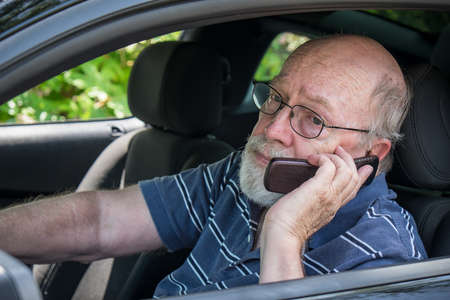 miserable: Closeup of elderly man in car calling for roadside assistance on cell phone  He looks hot and miserable