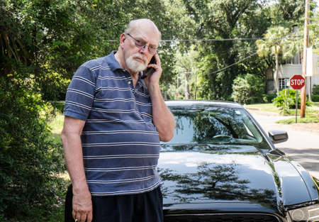 Angry senior man on cell phone calling for roadside assistance  Stock Photo