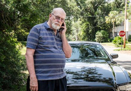 Angry senior man on cell phone calling for roadside assistance  Reklamní fotografie
