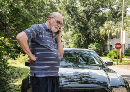 Angry elderly man on cell phone calls for roadside assistance for car malfunction or breakdown emergency  He looks unhappy and frantic