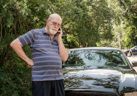 Angry elderly man on cell phone calls for roadside assistance for car malfunction or breakdown emergency