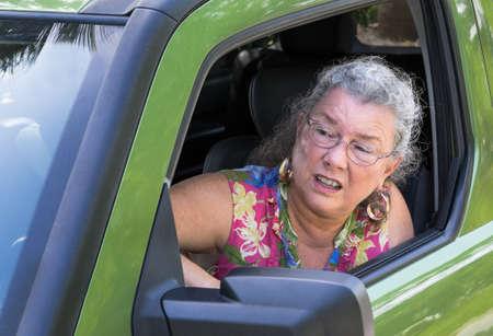 hot temper: Conductor Mujer mayor enojada con rabia en el camino gritando por la ventana del coche Foto de archivo