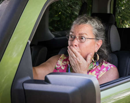 Sweaty, hot, senior woman driver looking terrified holding hand to mouth in driver