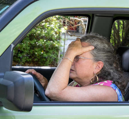 Closeup of senior woman driver holding her head in frustration, all stressed out