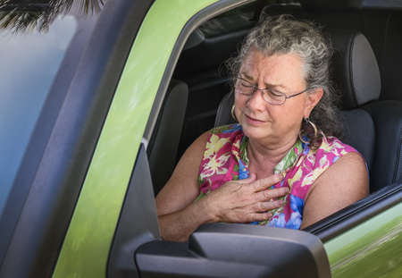 Sweaty hot senior woman winces with stress and chest pain while driving car