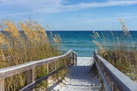 De zandige houten promenade leidt naar het strand Stockfoto