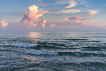 Sunset seascape at the Gulf of Mexico in Pensacola, Florida, colorful reflections, cumulus clouds, frothy breakers.