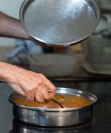 utencils: Short depth of field shot of mans hand stirring a pan of sauce on stove top