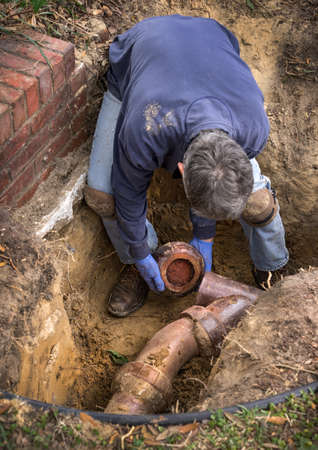 Man removing sections of old clogged clay ceramic sewer pipe in trench in the ground. Stock Photo