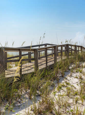 Rustic wooden boardwalk in hilly dunes at beach in Florida