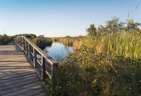 Old wooden arched footbridge at Fort Pickens in Gulf Islands National Seashore spans one of many canals along the long hiking path.