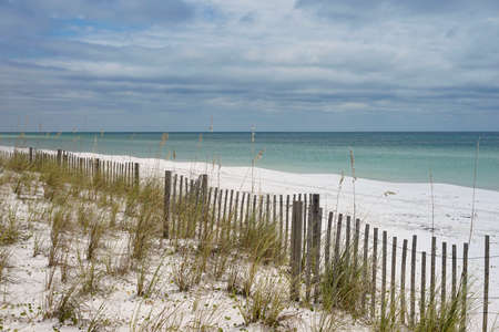 pensacola: Long sand fence runs along white sandy beach and dunes in Florida. Fence lessens effects of erosion from wind and water in the dunes. Stock Photo