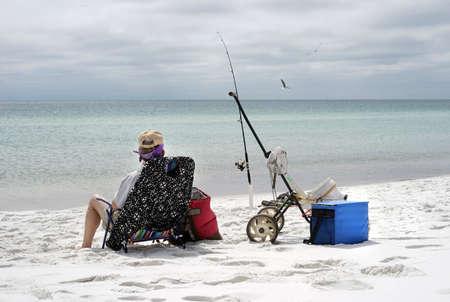 pesca: Relajado mujer madura la pesca en el Golfo de México, mirando al mar. Foto de archivo