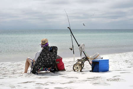 sea fishing: Relaxed mature woman fishing in the Gulf of Mexico, looking out to sea. Stock Photo