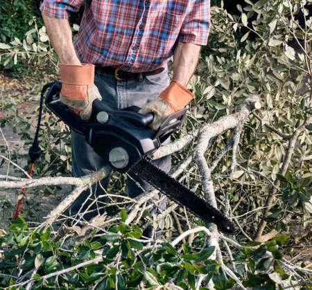 Close-up van de mens in handschoenen en snijden gevallen takken en bladeren puin met elektrische kettingzaag na een storm
