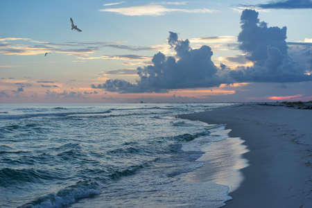 pensacola beach: Landscape of incoming tide in the Gulf of Mexico in tones of saturated blue and teal with pink sunset and puffy dark cumulus clouds. Stock Photo