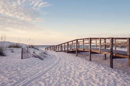 Wooden beach boardwalk through the sand dunes at dawn in soft pink light.